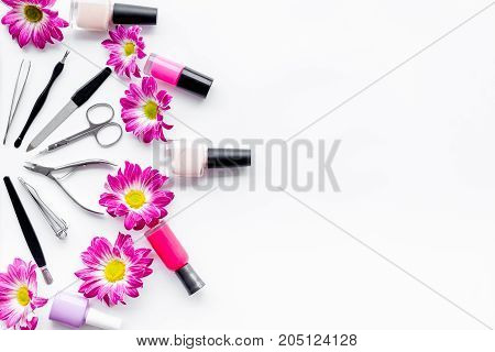 Preparing for manicure. Tools and nail polishes on white background top view.