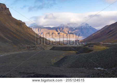 Svalbard - vast sedimentary rocks (limestone sandstone coal) in the glacial moraine of Longyear valley showing rich geological diversity. Longyearbyen Adventfjorden and mountain Hiorthfjellet in background.