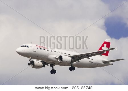 LONDON UK - AUGUST 8 2013; A Swiss Air AirBus A320 lands on a cloudy day at Heathrow Airport