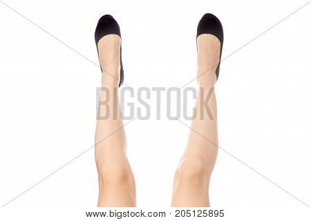 Female legs feet black shoes on white background isolation