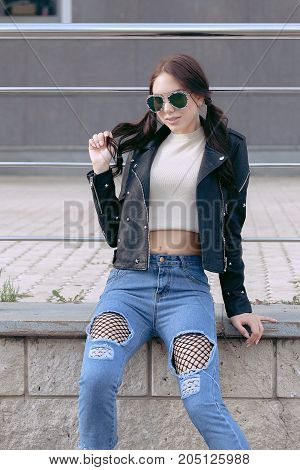 fashionable young woman in rock style clothes, black leather jacket, blue jeans, tights in a grid under battered jeans.