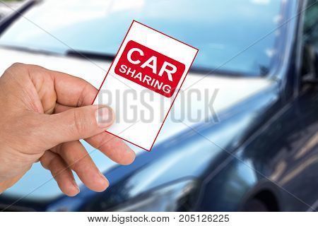 Hand Holding Car Sharing Card In Front Of Car