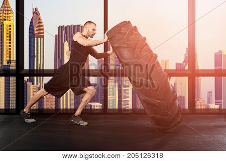 Young Muscular Man Pushing Tire In Gym With City Skyline Seen Through Window