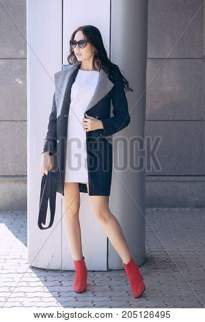 Outdoor portrait of a young beautiful fashionable woman, outdoors. A model dressed in a stylish gray coat, sunglasses. The concept of women's fashion, urban lifestyle.