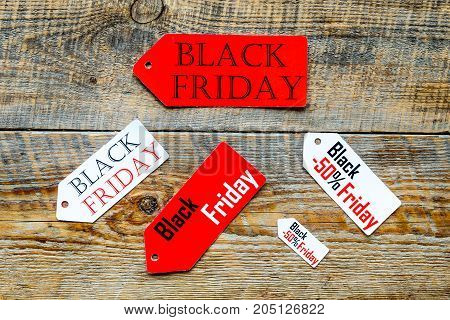 Words black friday on colored labels on wooden background top view.