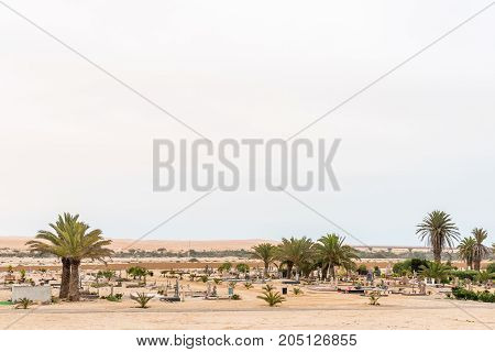 The cemetery in Swakopmund in the Namib Desert on the Atlantic Coast of Namibia. The road bridge over the Swakop River and sand dunes are in the back