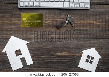 work desk with keyboard, keys and paper house figures for selling house set wooden background top view space for text