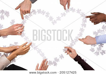 Group Of Hands Making Heart Shape With Jigsaw Puzzles Over White Background