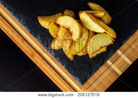 Potato food . Baked potatoes with spices and salt on black wooden table. Free space for text. Top view