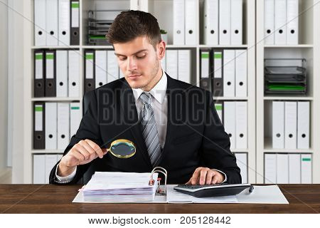 Young Businessman Analyzing Bill With Magnifying Glass At Workplace
