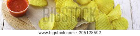 Horizontal bakground of potato chips on a white table