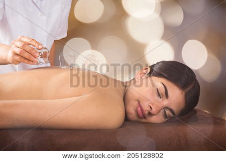 Close-up Of A Therapist Placing Transparent Glass Cups On Relaxed Young Woman's Back