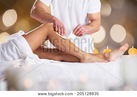 Close-up Of A Therapist Waxing Female Customer's Leg With Wax Strip