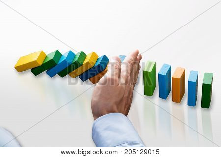 Businessperson Stopping Multi Colored Dominoes From Falling On Desk