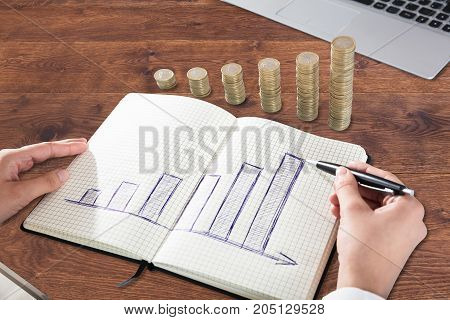 Businessperson Drawing Graph On Note Book With Stacked Coins Over Desk
