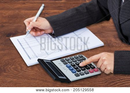 Businessperson's Hand Calculating Bill Over Wooden Desk