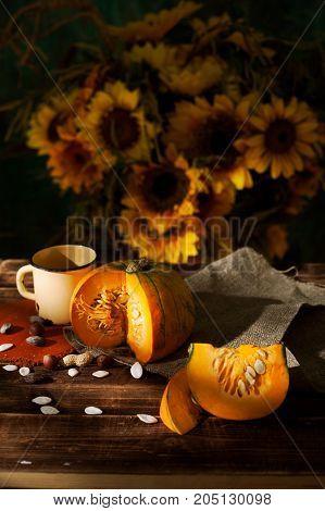 autumn still life with pumpkin mug sunflower seeds on tablecloths and table