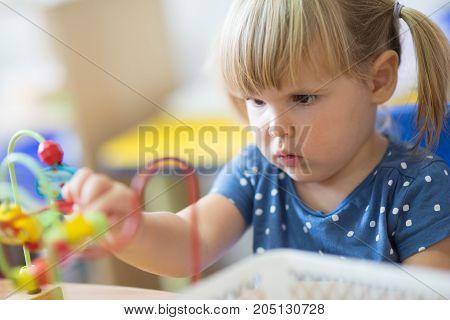 Portrait of little blondie girl solves puzzle