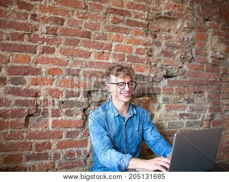 Cheerful young businessman working in internet via portable laptop computer. Happy hipster guy successful freelancer using net-book