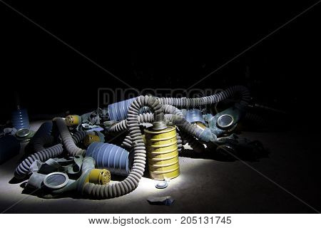 A bunch of hoses, gas masks and filters in dark room