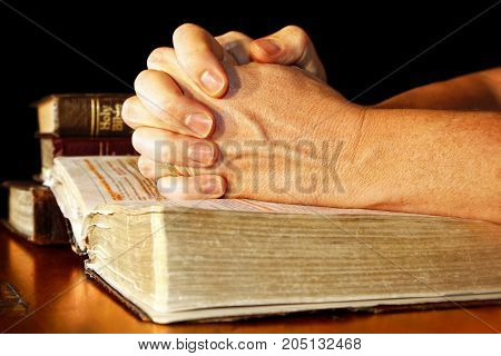A man folds his hands in committed prayer over a Holy Bible while light shines directly on his hands and the open bible.