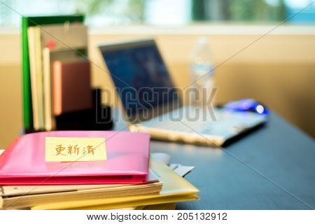 Updated; Stack Of Documents And Laptop At Working Desk.