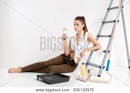 attractive woman painting  wall in her house. beautiful woman holding a paint brush