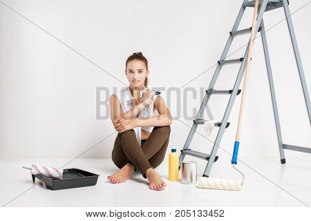 smiling woman painting  wall in her house. beautiful woman holding a paint brush