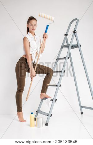 beautiful attractive woman ready to paint wall with paint roller in house