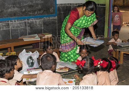 PONDICHERY PUDUCHERY INDIA - STEPEMBER 04 2017. Unidentified children boys girls with school uniform study in classroom with teacher help with books. Government public school.