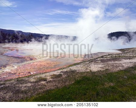 Steaming hot spring at Yellowstone National Park sulfurous vapor rising the water heavy with minerals.