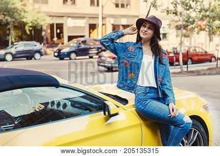 girl leaned against a yellow car. coquettish young woman on the street. blurred urban background. copy space for your text