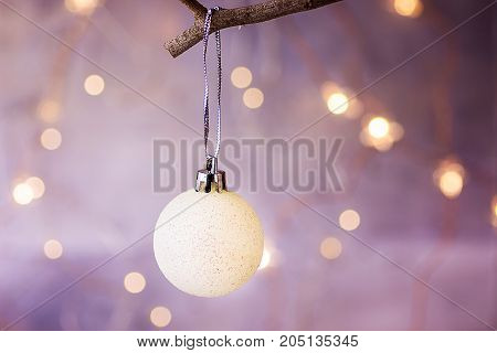 White Christmas Tree Ball Hanging on a Branch Golden Garland Glittering Lights in the background Festive Greeting Card Poster Template Copy Space