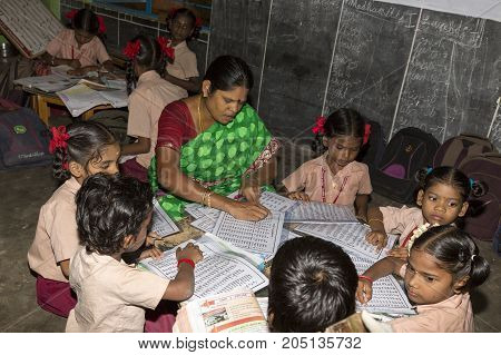 PONDICHERY PUDUCHERY INDIA - STEPEMBER 04 2017. Unidentified children boys girls with school uniform study in classroom with teacher help with books. Government public school.