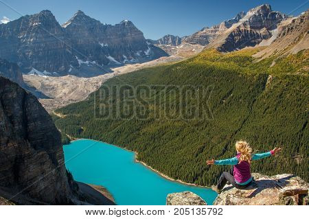 Blond hair young female hiker at the top of Tower of Babel above Moraine Lake, Banff NP, Canada