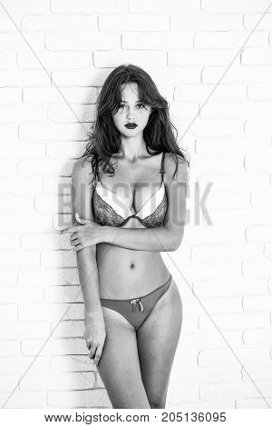 Young girl with pretty face dark hair fashion makeup in sexy underware gray sexy bra with lace and panties standing on white wall background studio