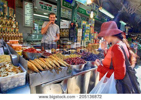 TEL-AVIV, ISRAEL- APRIL 3, 2016: Street vendor is selling green and black olives in the oriental market Carmel, Tel Aviv, Israel