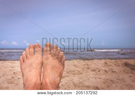 Close up of a feet of a man lying on the beach in summer