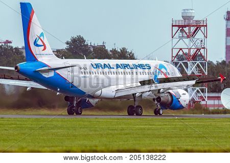 Pulkovo, Saint-Petersburg, Russia - August 10, 2017:   The airplane Airbus A319 of Ural Airlines is moving on the runway against the background of the forest and blue sky. Summer sunny weather