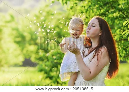woman and child blowing on a dandelion against a background of green trees with shallow depth of field