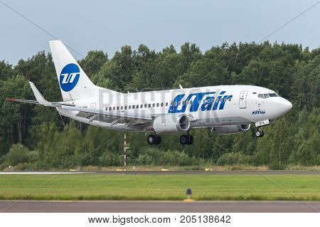 Pulkovo, Saint-Petersburg, Russia - August 10, 2017:   The airplane  Boeing B737 of UTair airlines is landing on the runway against the background of the forest
