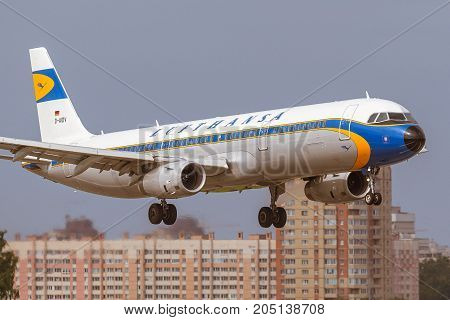 Pulkovo, Saint-Petersburg, Russia - August 10, 2017:   The airplane  Airbus A321 of Aeroflot  airlines is landing on the runway against the background of the city skyline. Has a special retro livery