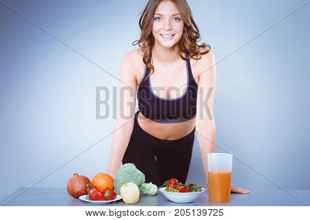 Young and beautiful woman standing near desk with vegetables