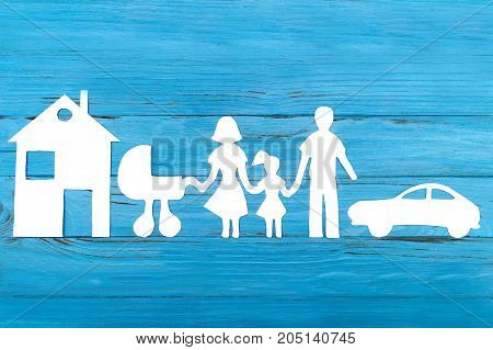 Paper silhouette of family with baby carriage, house and car on blue wooden background. Life insurance concept