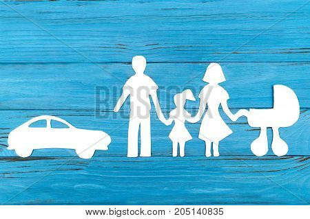 Paper silhouette of family with baby carriage and car on blue wooden background. Life insurance concept