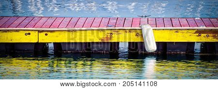 A boat bumper sits out on a colorful southern California dock.