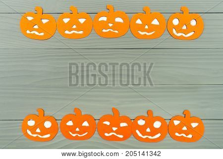 Horizontal frame with different pumpkin paper silhouettes on a gray wooden table. Halloween celebration. Copy space for greetings