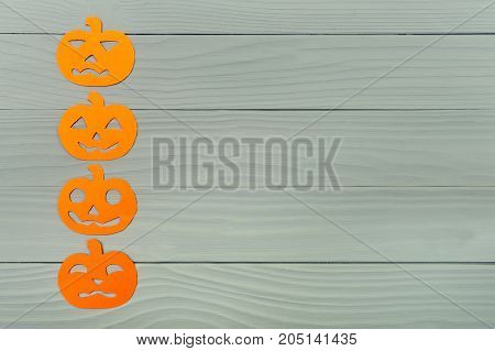 Top view of paper silhouette of four different pumpkin left vertically on grey wooden background. Halloween holiday background. Copy space