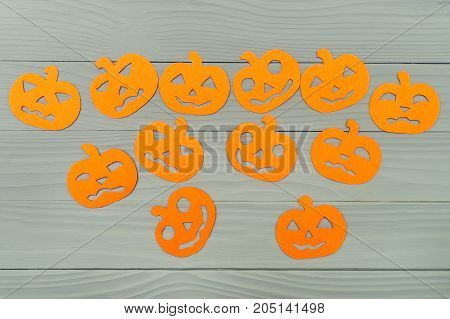 Many different halloween pumpkin paper silhouettes on a gray wooden board. Halloween celebration