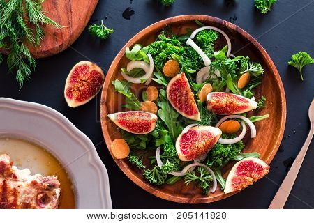 Autumn salad of arugula, figs in a brown earthenware plate on a dark background.
